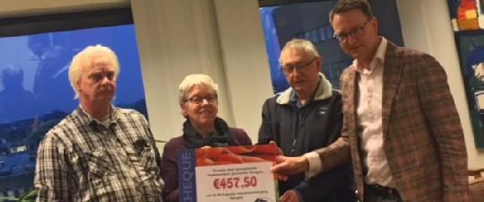 Wethouder Bruggink overhandigt de opbrengst € 457,50 van de kerstmarkt aan het bestuur.