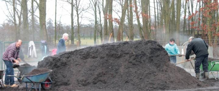 Een lading aangeleverde compost wordt over de moestuin verdeeld.